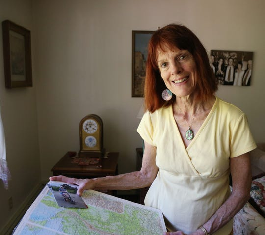 Gloria Ghedini searches an atlas for the town one of her pen pals lives in while at her home in Pleasant Valley on September 13, 2018.