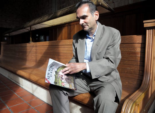 Tom Martinelli thumbs through the 15th anniversary edition of New York By Rail magazine at Poughkeepsie train station on September 13, 2018.