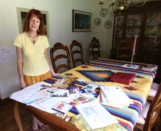 Gloria Ghedini looks over her table with a selection of souvenirs and letters she has received from pen pals over the years at her home in Pleasant Valley on September 13, 2018.