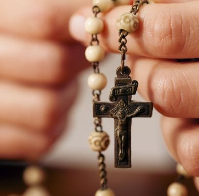 Hands holding a crucifix and rosary