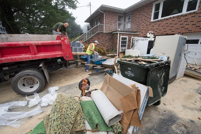 A pile of appliances wait for recycling outside the Boyer home while workers unload cement block to repair the basement wall Monday.