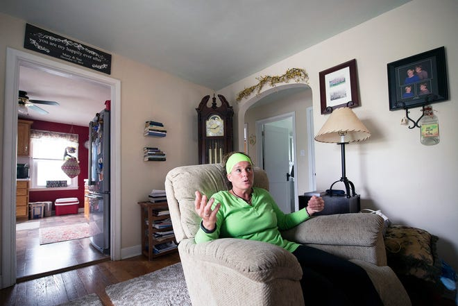 """Surrounded by wedding photos with her wife Sue and a wall plaque that says """"you are my happily ever after"""" at her home in Berks County, clergy abuse survivor Mary McHale talks about how the abuse began when she was in high school. After confiding in a priest that she was gay, he offered therapy where they both took off their clothing."""