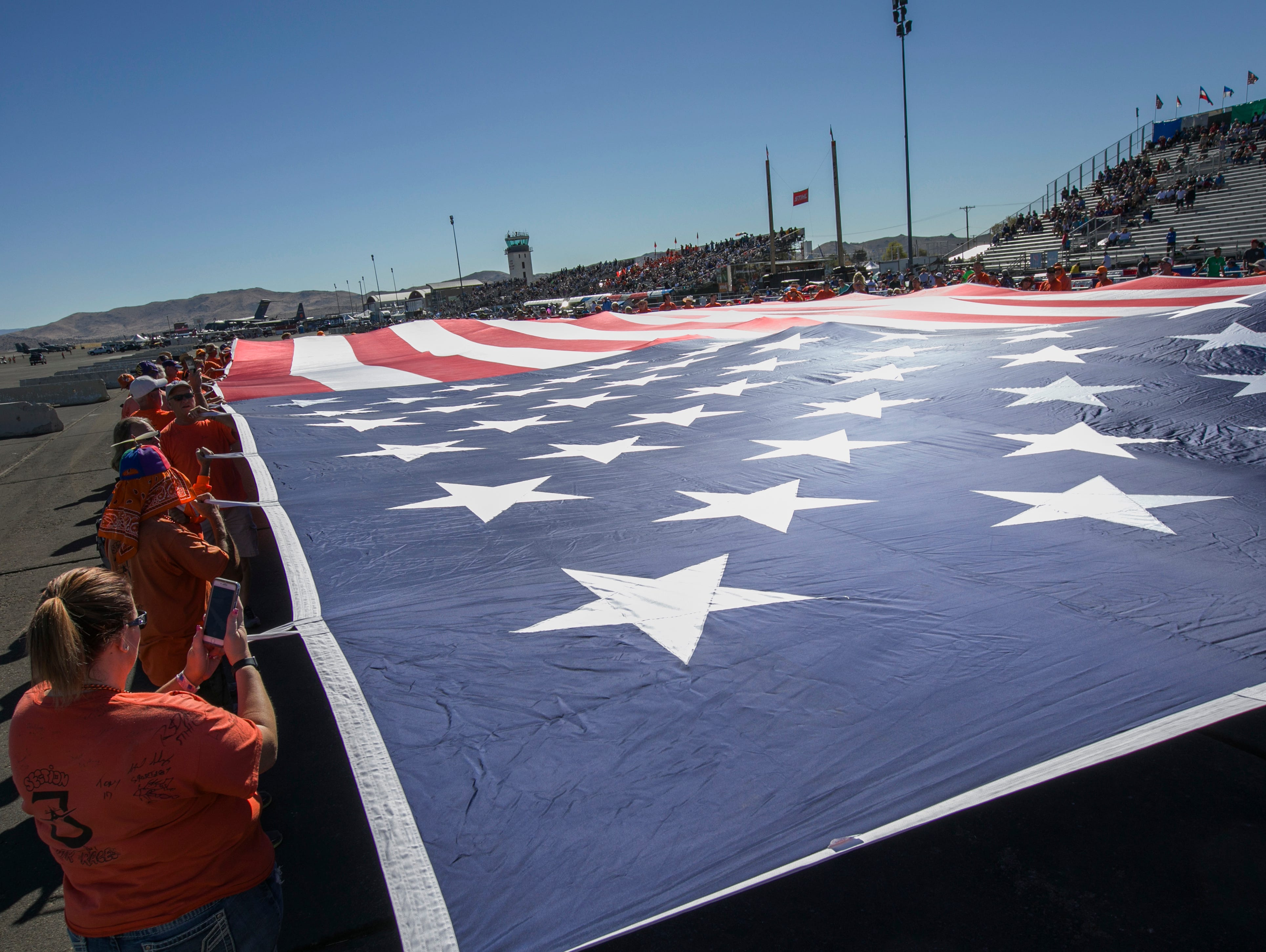 Members of section 3 hold a giant flag during the Reno National Championship Air Races on Sunday, Sept. 16, 2018.