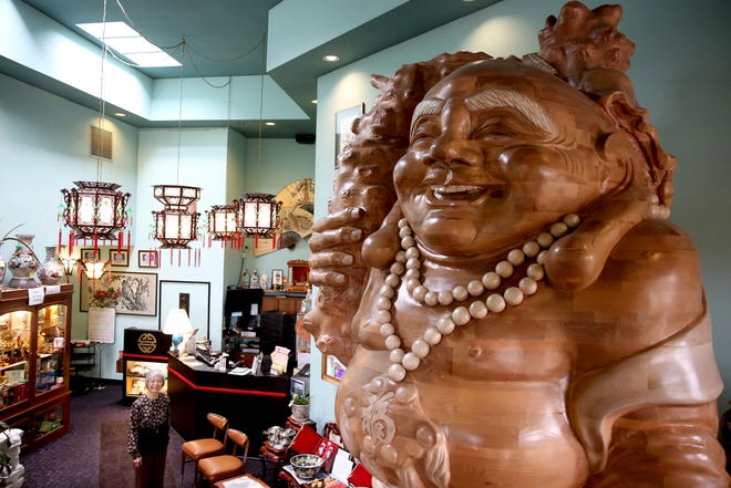 Bo Kwan stands for a photo with the wooden Buddha statue in the front lobby and gift shop portion of Kwan's Cuisine in Salem on Monday, Sep. 17, 2018. The Chinese restaurant closed September 2 after her husband, chef Kam Sang Kwan, died over the summer.