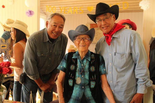Dr. Marian Lowe, center, celebrates her 100th birthday with two of her sons, Gregory Lowe, left, and Galen Lowe, right, Saturday, Sept. 15, 2018. The party was cowboy themed, and guests were given hats, bandanas and sticker mustaches to wear.