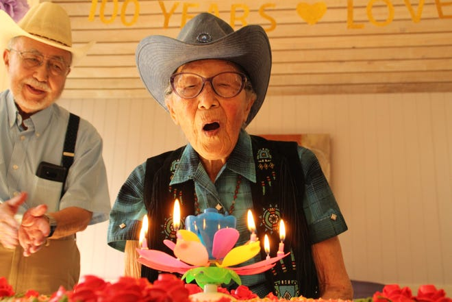 Dr. Marian Lowe blows out the candles on her birthday cake Saturday, Sept. 15, 2018. More than 50 members of her family gathered to celebrate Lowe's 100th birthday.