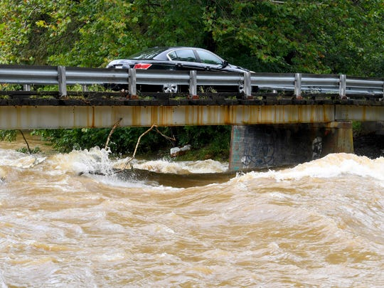 A car travels slowly across a bridge over Back Creek, which churns and rolls as it runs high underneath, on Howardsville Turnpike in Sherando on Monday, Sept. 17, 2018.