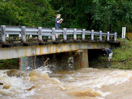 A boy stands on the safety of the bridge  on Howardsville Turnpike. They watch the waters of Back Creek churn and roll as it runs high in Sherando on Monday, Sept. 17, 2018.