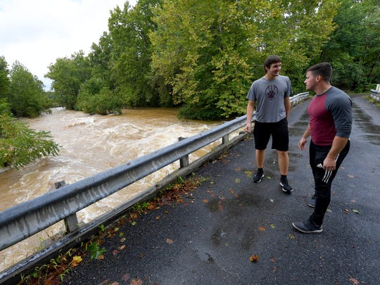 Ryan Marshall, 17, (left) and Jacob Lipsomb stand on a bridge over on Howardsville Turnpike, watching the waters of Back Creek churn and roll as the creek runs high in Sherando on Monday, Sept. 17, 2018.
