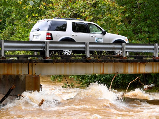 An SUV travels slowly across a bridge over Back Creek, which churns and rolls as it runs high underneath, on Howardsville Turnpike in Sherando on Monday, Sept. 17, 2018.