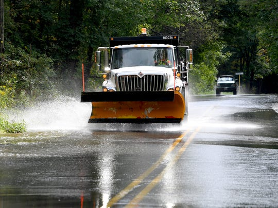 A dump truck with a snowplow raised travels through water flowing across Mt. Torrey Road near Sherando on Monday, Sept. 17, 2018.