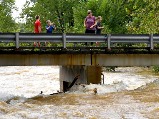 A woman and three boys stand on the safety of the bridge  on Howardsville Turnpike. They watch the waters of Back Creek churn and roll as it runs high in Sherando on Monday, Sept. 17, 2018.