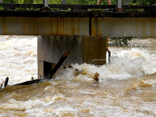 Debris collects against one of the bridge's upright supports as Back Creek churns, rolls and runs high under the bridge on Howardsville Turnpike in Sherando on Monday, Sept. 17, 2018.