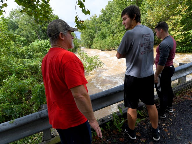 James Lipsomb (left) stands on a bridge over on Howardsville Turnpike. He joins Ryan Marshall, 17, and Jacob Lipsomb in watching the waters of Back Creek churn and roll as it runs high in Sherando on Monday, Sept. 17, 2018.