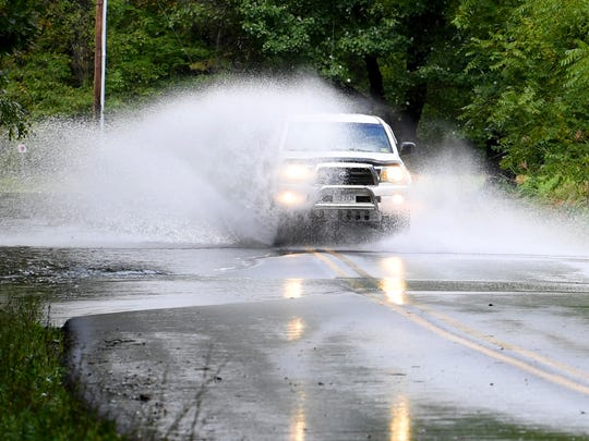 A vehicle kicks up water as it travels through water flowing across Mt. Torrey Road near Sherando on Monday, Sept. 17, 2018.