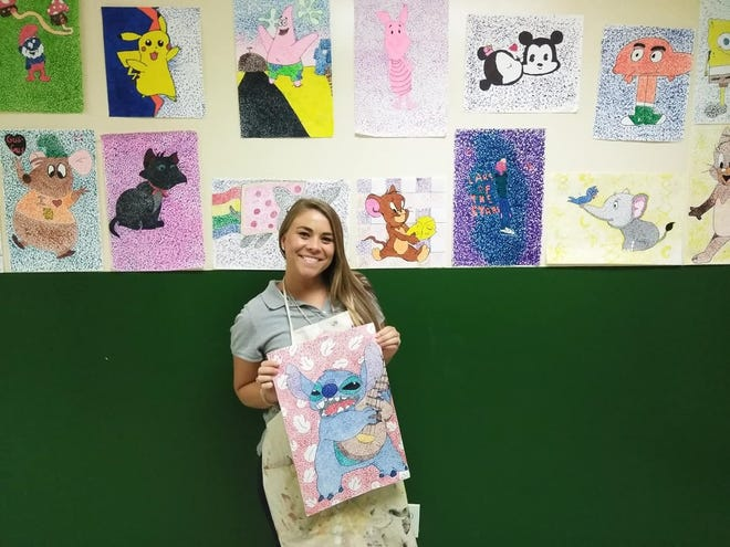 Ashley Warren, Renaissance Charter middle school art teacher, shows off her students' Pointillism works of art for International Dot day.