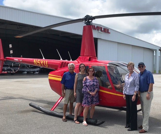 Butch Bayley, Kathy Lockhart and Sue Whittington, all of Stuart-Sunrise Rotary join helicopter pilot Tom Bright, Monarch Country Club General Manager Beth David and Monarch Country Club Golf Pro Bo Preston in preparing for the Helicopter Ball Drop.