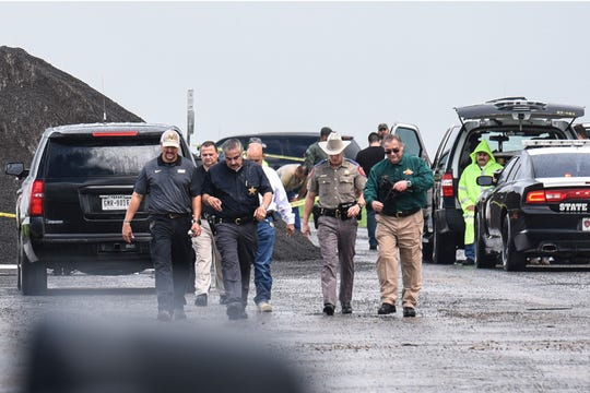 """Law enforcement officers gather near the scene where the body of a woman was found near Interstate 35 north of Laredo, Texas on Saturday, Sept. 15, 2018. A U.S. Border Patrol agent suspected of killing four women was arrested early Saturday after a fifth woman who had been abducted managed to escape from him and notify authorities, law enforcement officials said, describing the agent as a """"serial killer."""""""