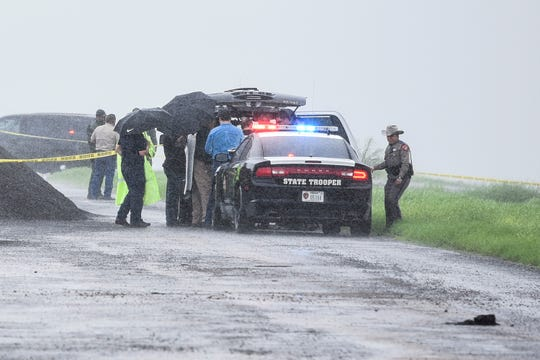 "Law enforcement officers gather near the scene where the body of a woman was found near Interstate 35 north of Laredo, Texas on Saturday, Sept. 15, 2018. A U.S. Border Patrol agent suspected of killing four women was arrested early Saturday after a fifth woman who had been abducted managed to escape from him and notify authorities, law enforcement officials said, describing the agent as a ""serial killer."""