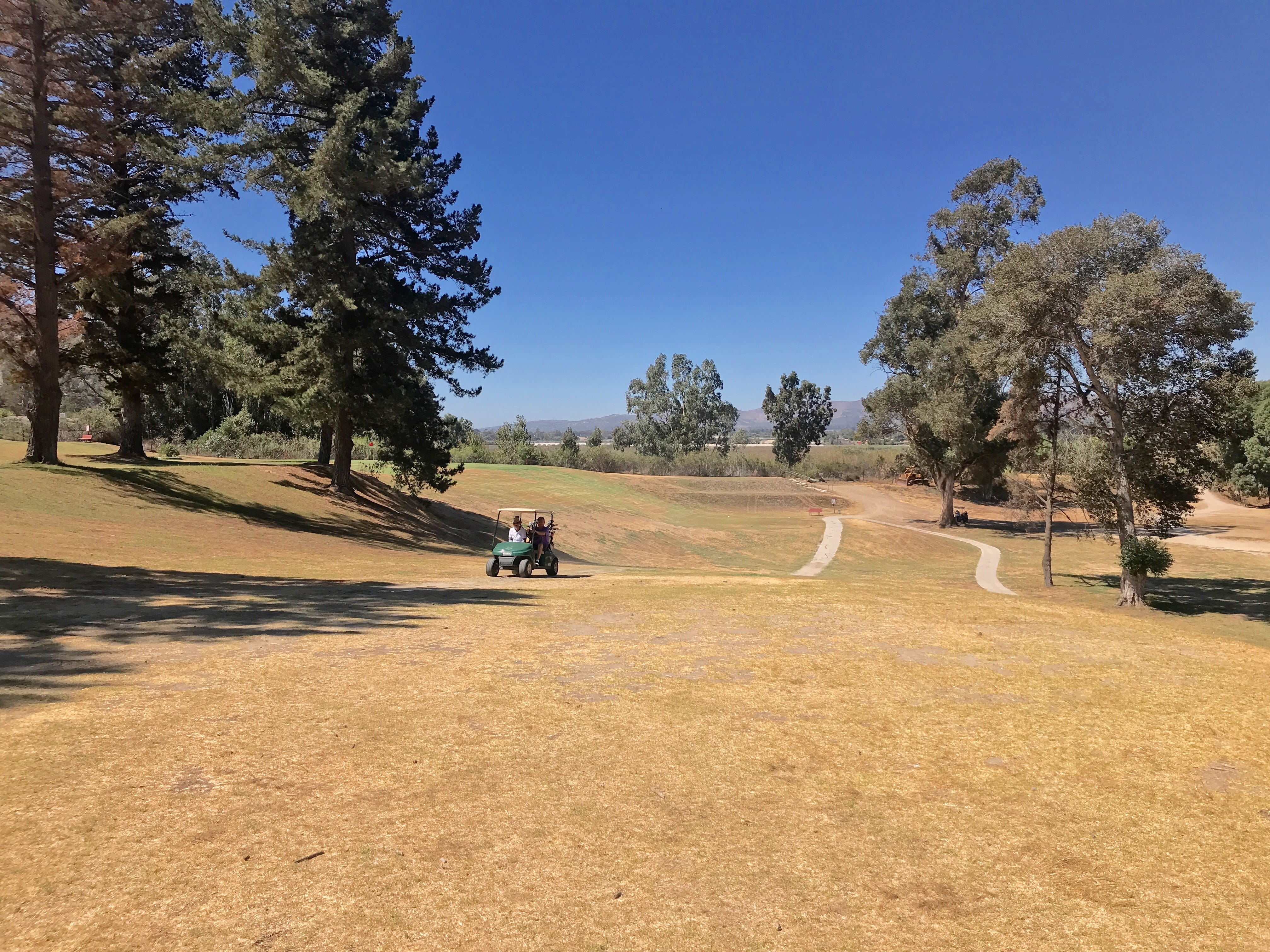 Local golf enthusiasts trundle up a brown fairway at the Mountain View Golf Course in Santa Paula, which is up for sale.
