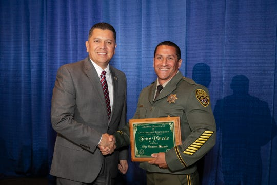 Tony Pinedo, right, a Ventura Youth Correctional Facility officer, stands with Ralph Diaz, secretary of the California Department of Corrections and Rehabilitations, at an awards ceremony Friday.