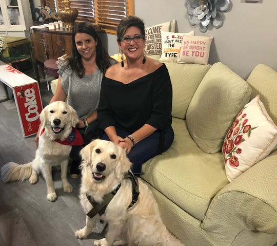 Heather Brimacombe, left, and Angela Lentz sit with their dogs Fletcher and Frankie inside their new business, the Frankie & Fletcher Mercantile.