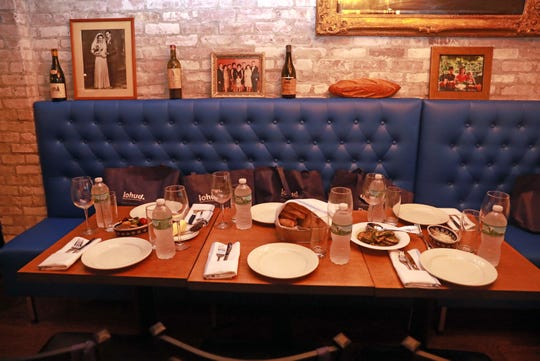 """The table is set for """"Dinner with Jeanne"""" at Maria Restaurant in New Rochelle with a photo of Maria Cucullo and other family photos displayed just above the blue banquette. Photographed Sept. 14, 2018."""
