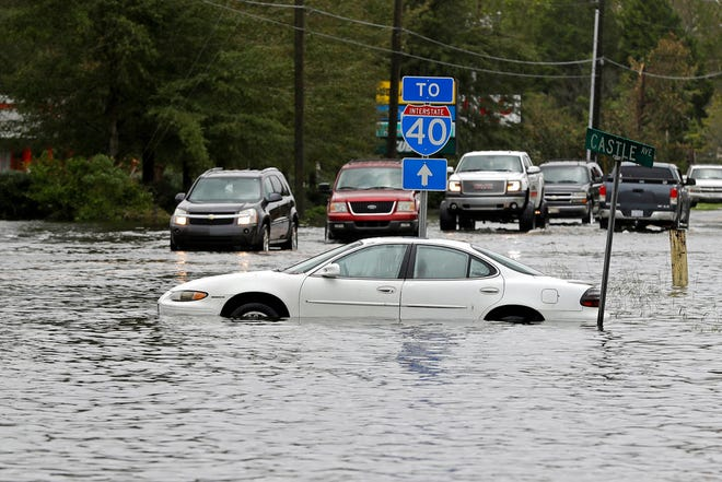 Cars try to navigate a flooded road leading to Interstate 40 in Castle Hayne, N.C., after damage from Hurricane Florence cut off access to Wilmington, N.C., Sunday, Sept. 16, 2018.