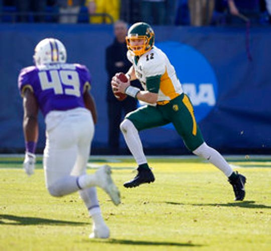 North Dakota State quarterback Easton Stick (12) runs up the field as James Madison linebacker Brandon Hereford (49) closes in on him during the first half in the FCS championship NCAA college football game at Toyota Stadium in Frisco, Texas.