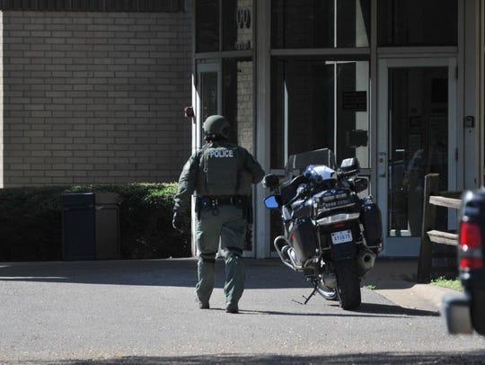 A Wichita Falls police officer walks toward Midtown Manor Apartments in the 400 block of Burnett Street on Monday, Sept. 17, 2018.