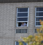 A resident of Midtown Manor watches as police search for a possible suspect in a stabbing that occurred at or near the complex Monday morning.