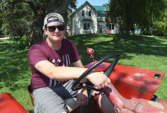 Zach Koser poses on a tractor on his hobby farm near Lake Crystal, Minn. Instead of enrolling in college, Koser took his college savings and bought the farm.