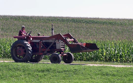 Zach Koser drives his tractor up a gravel road in front of his home near Lake Crystal, Minn.