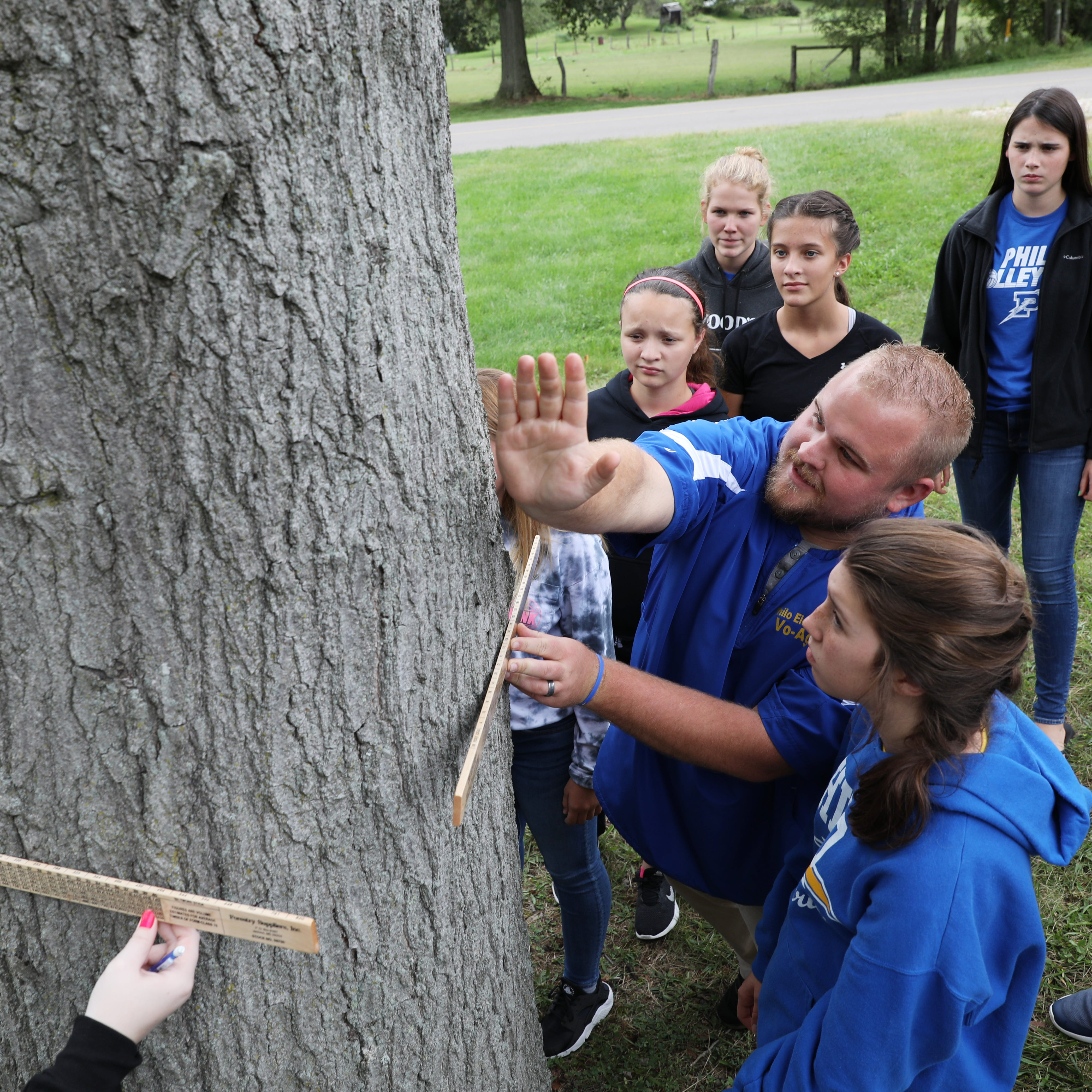 Philo High School vocational ag teacher Clay Winland shows a group of students how to use a board-foot measuring stick while measuring a tree near the school.