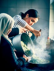 Duchess Meghan of Sussex knows her way around a kitchen. She's written the foreword to a charity cookbook by the women in the Hubb Community Kitchen, shown here with Meghan helping prepare traditional recipes at the Al Manaar Muslim Cultural Heritage Centre in West London.