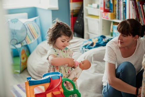 An older sibling can practice caring for and being gentle with a newborn before  baby arrives by pretending with a doll.