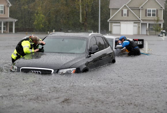 Members of the North Carolina Task Force urban search and rescue team check cars in a flooded neighborhood looking for residents who stayed behind as Florence continues to dump heavy rain in Fayetteville, N.C. on Sept. 16, 2018.