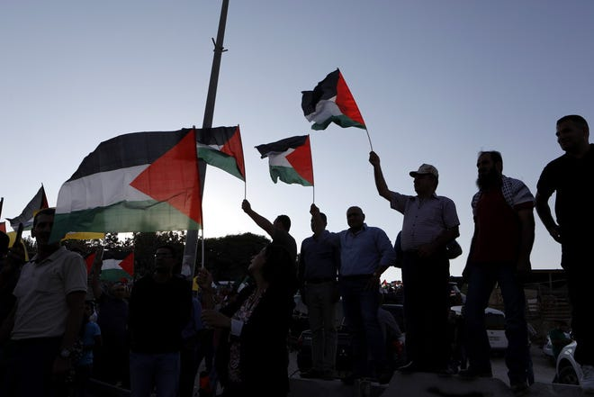 Demonstrators wave Palestinian flags in front of Israeli troops as they protest against Israel's plan to demolish the Palestinian Bedouin village of Khan al-Ahmar, located between the West Bank city of Jericho and Jerusalem near the Israeli settlement of Maale Adumim, 16 September 2018.