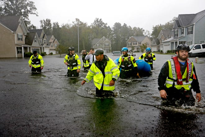 Members of the North Carolina Task Force urban search and rescue team wade through a flooded neighborhood looking for residents who stayed behind as Florence continues to dump heavy rain in Fayetteville, N.C. on Sept. 16, 2018.