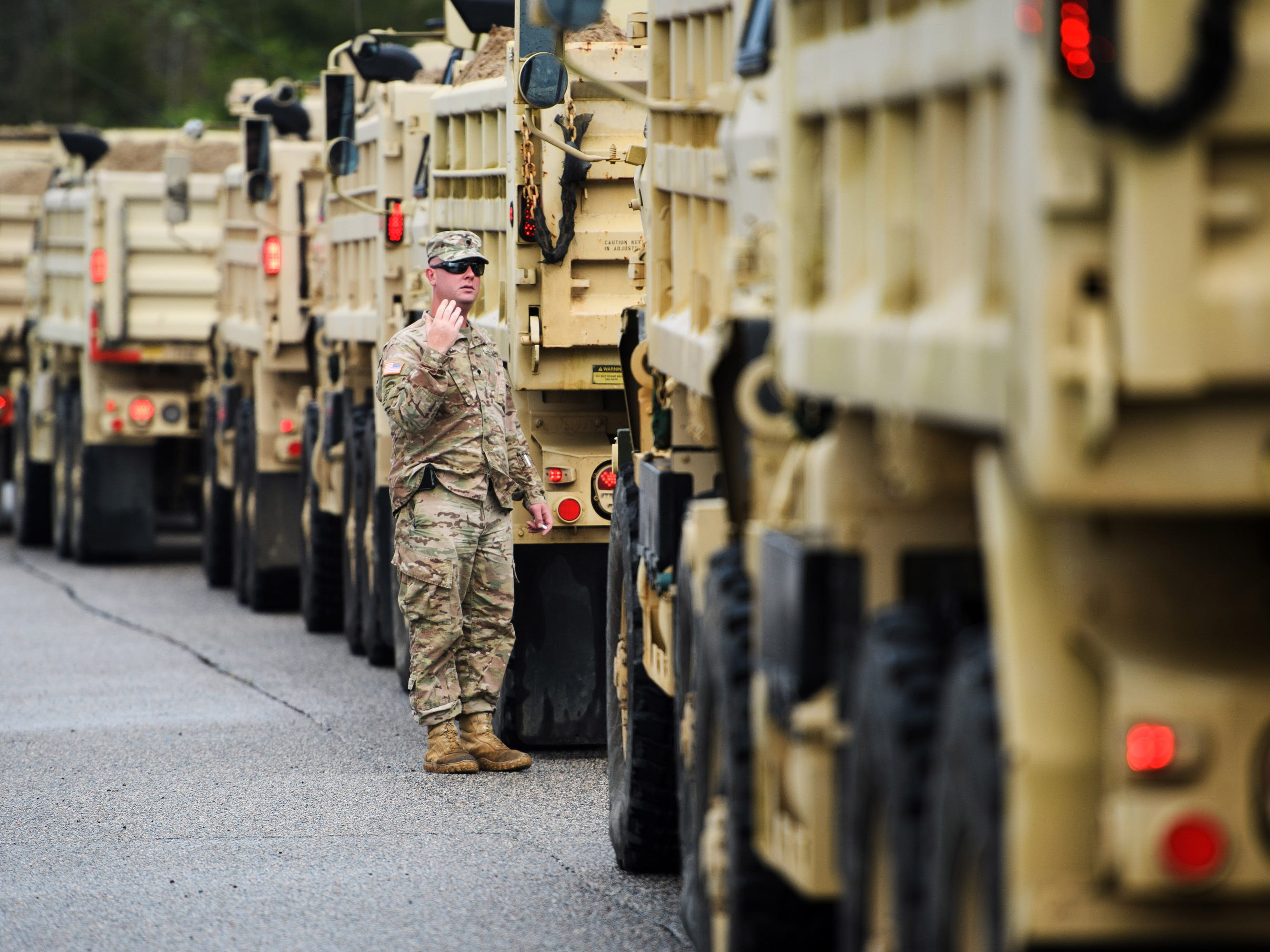 A South Carolina Army National Guardsman directs trucks full of sand along U.S. 501 South outside of Conway, N.C. in preparation of rising water levels on the Waccamaw River on Sept. 16, 2018.