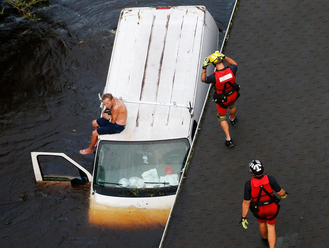 U.S. Coast Guard rescue swimmer Samuel Knoeppel, center, and Randy Haba, bottom right, approach  Willie Schubert holding a dog while he is a stranded on a van in Pollocksville, NC. Sept. 17, 2018, in the aftermath of Hurricane Florence.