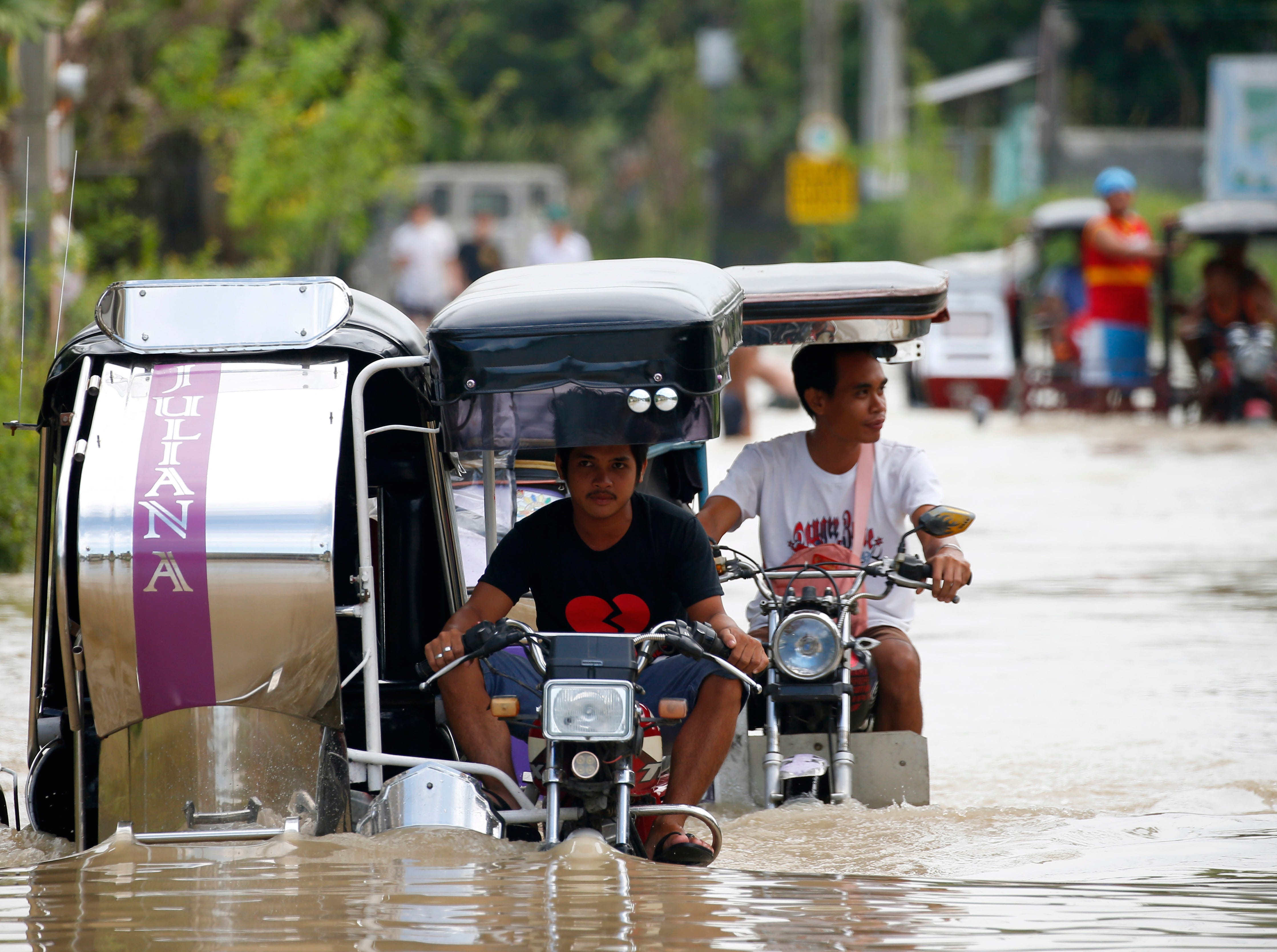 People travel through a flooded road brought about by Typhoon Mangkhut which barreled into northeastern Philippines during the weekend and inundated low-lying areas in its 900-kilometer wide cloud band, Monday, Sept. 17, 2018 in Calumpit township, Bulacan province north of Manila, Philippines. A Philippine mayor says it's highly unlikely any of the 40 to 50 people who are feared buried in a mudslide set off by Typhoon Mangkhut can be found alive.