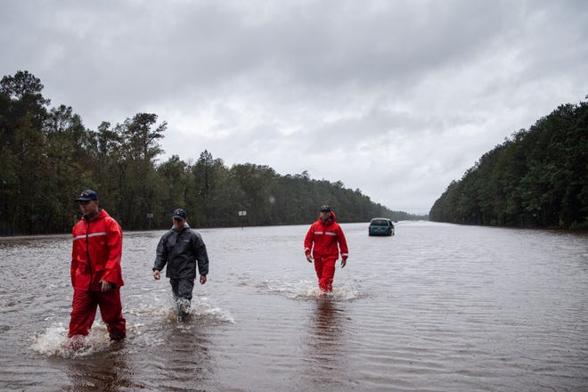 Coast Guard rescuers check on abandoned cars on Sept. 16, 2018, near Hallsboro, North Carolina.