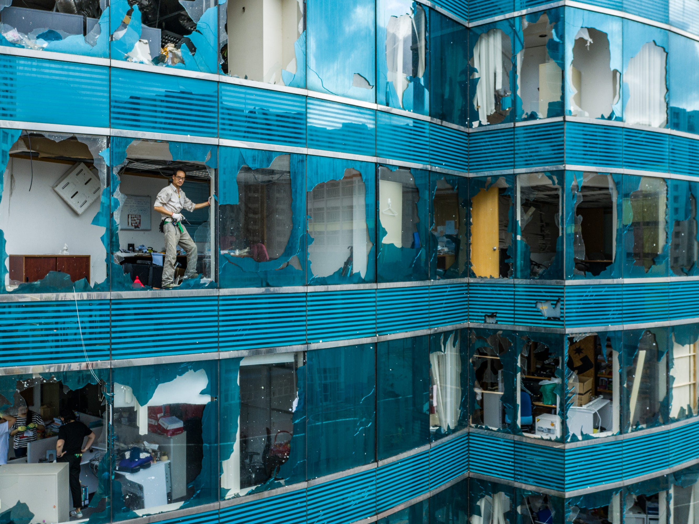 A man stands in a window of a heavily damaged building in the aftermath of Typhoon Mangkhut on September 17, 2018 in Hong Kong.