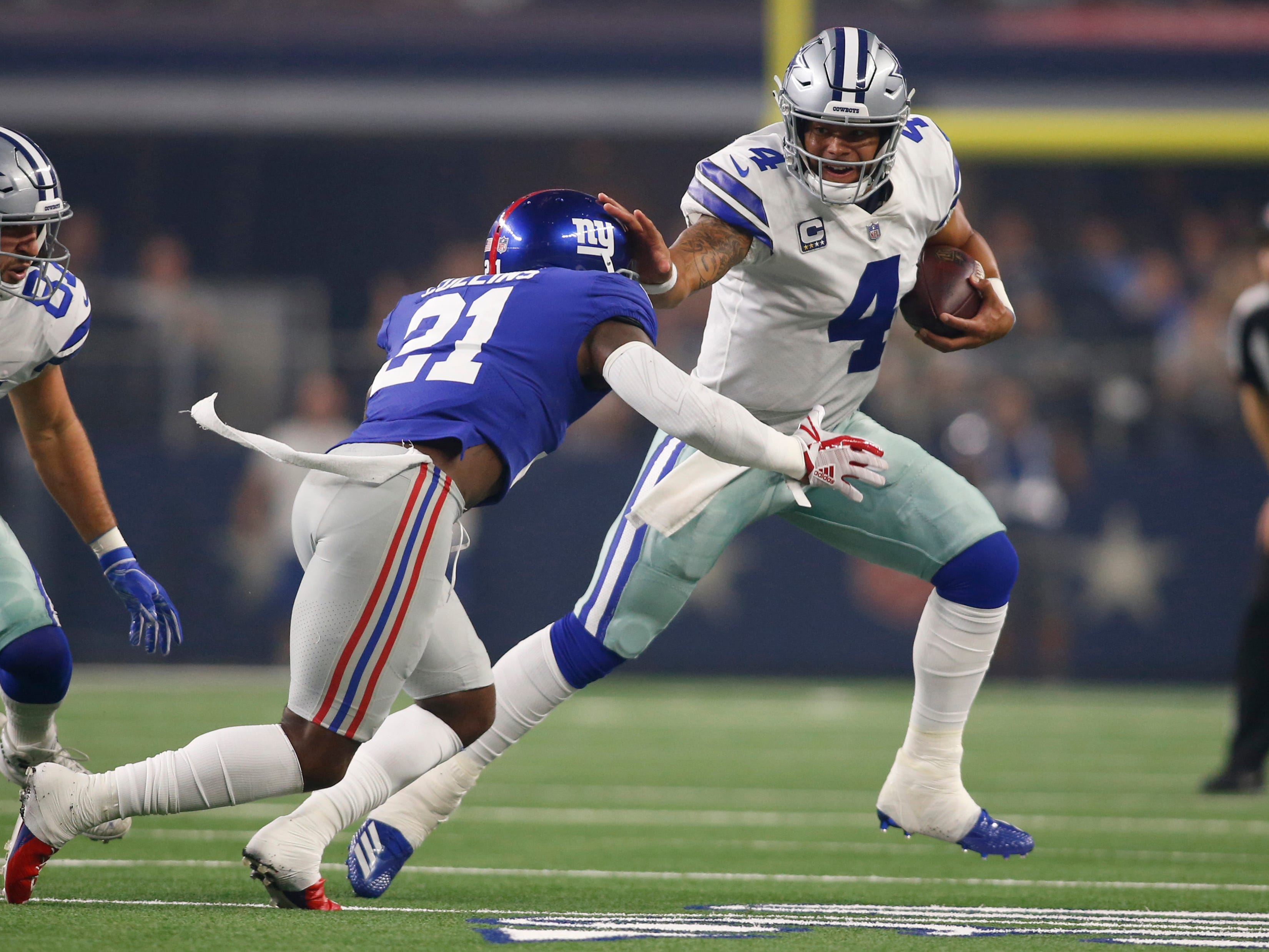 Sep 16, 2018; Arlington, TX, USA; Dallas Cowboys quarterback Dak Prescott (4) stiff arms New York Giants defensive back Landon Collins (21) in the first quarter at AT&T Stadium. Mandatory Credit: Tim Heitman-USA TODAY Sports