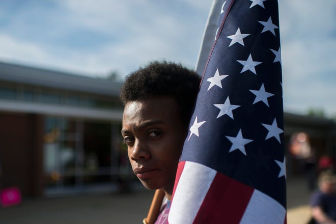 John Larrier of Maplewood stands with an American Flag as protestors gather before a town hall meeting from Congressman Tom MacArthur (R-NJ) Wednesday, May 10, 2017 in Willingboro. (Via OlyDrop)