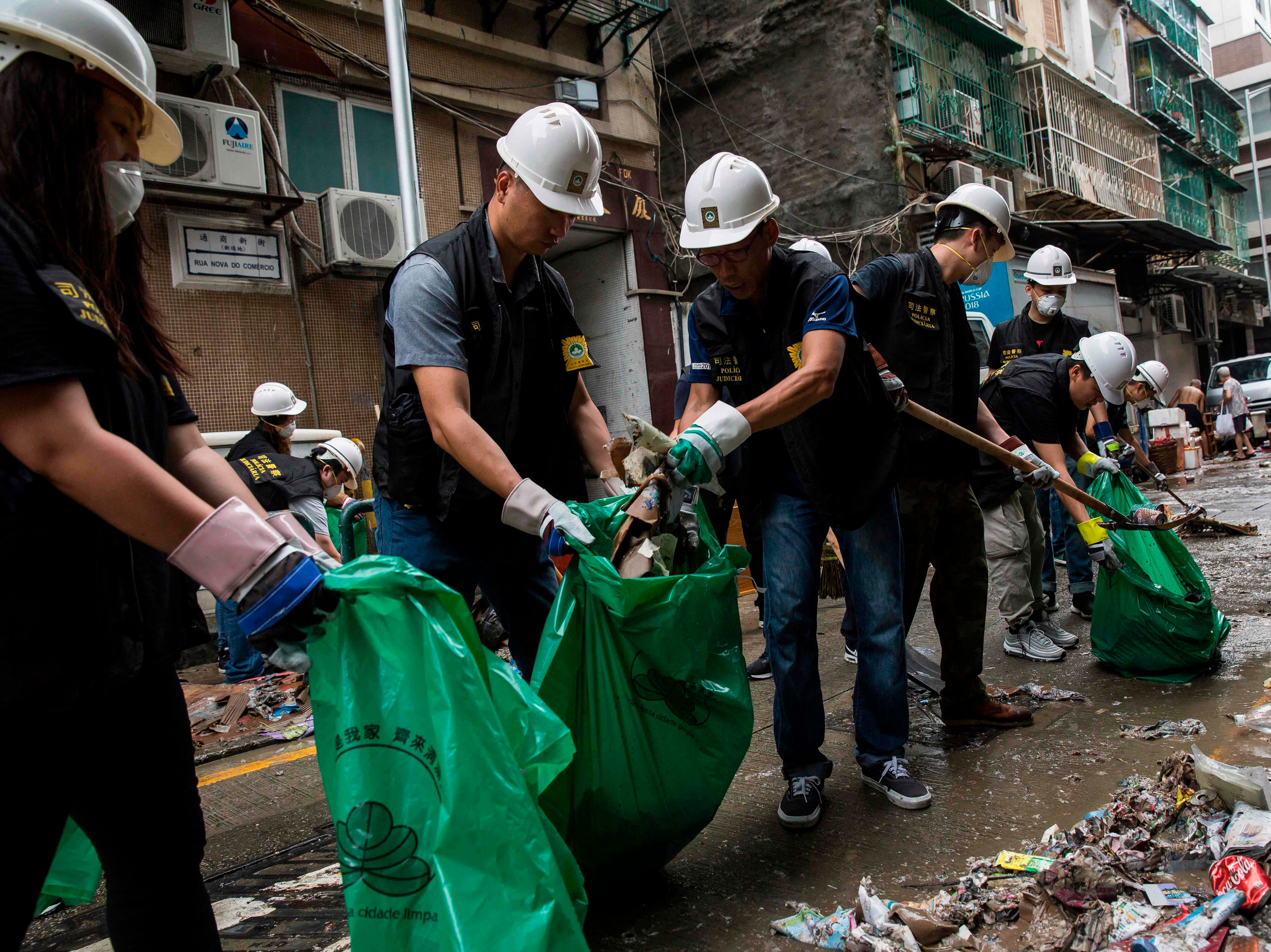 Police clear rubbish and debris from a street a day after Typhoon Mangkhut hit Macau on Sept. 17, 2018.