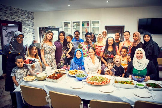 Duchess Meghan of Sussex poses with women in the Hubb Community Kitchen at the Al Manaar Muslim Cultural Heritage Centre in West London, in the aftermath of the Grenfell Tower fire. - The women have published a cookbook 'Together: Our Community Cookbook' with a foreword by Meghan.