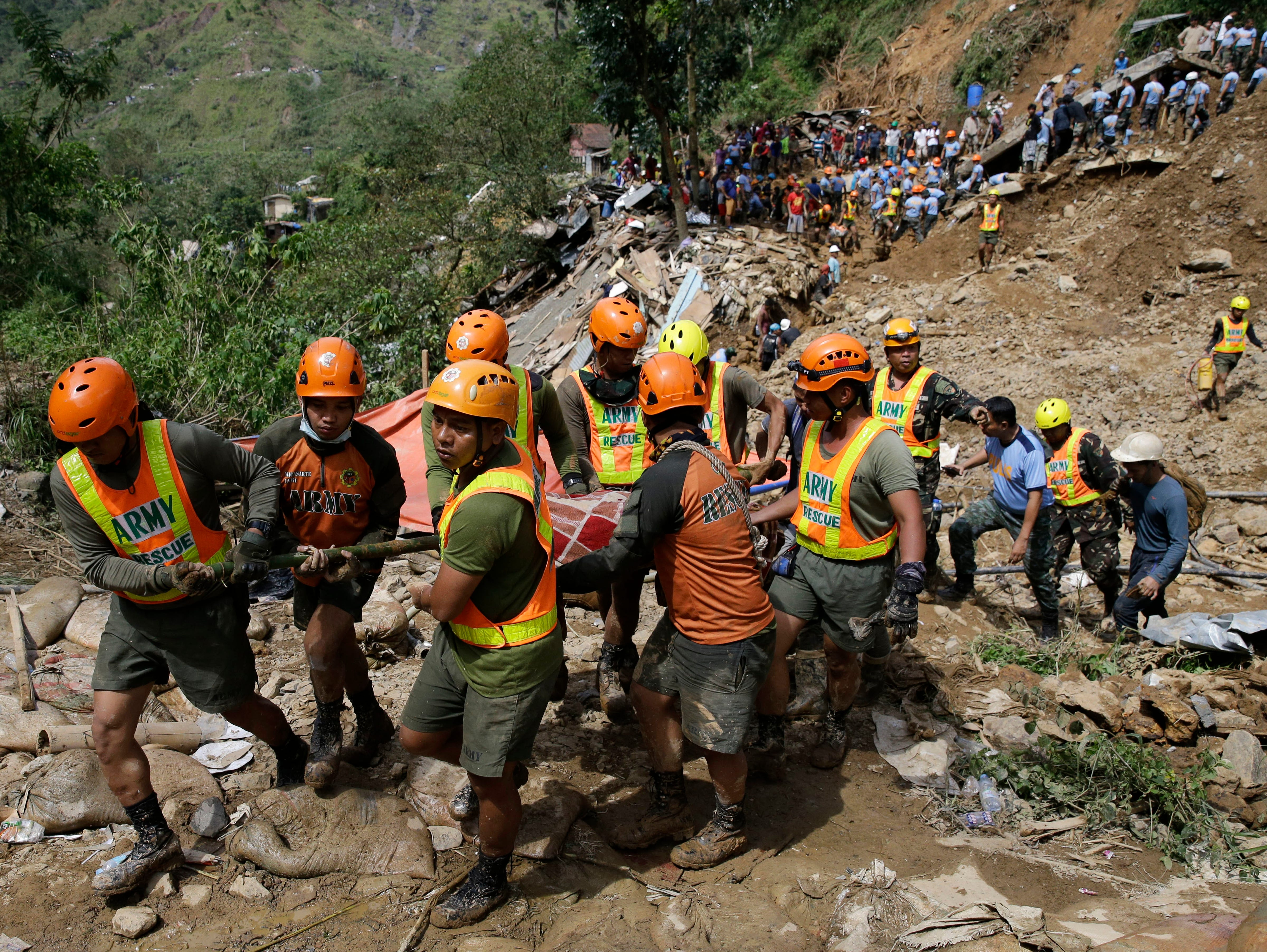 Rescuers carry a body recovered from a landslide caused by Typhoon Mangkhut in Itogon, Benguet province, northern Philippines on Monday, Sept. 17, 2018. Itogon Mayor Victorio Palangdan said that at the height of the typhoon's onslaught Saturday afternoon, dozens of people, mostly miners and their families, rushed into an old three-story building in the village of Ucab. The building, a former mining bunkhouse that had been transformed into a chapel, was obliterated when part of a mountain slope collapsed.
