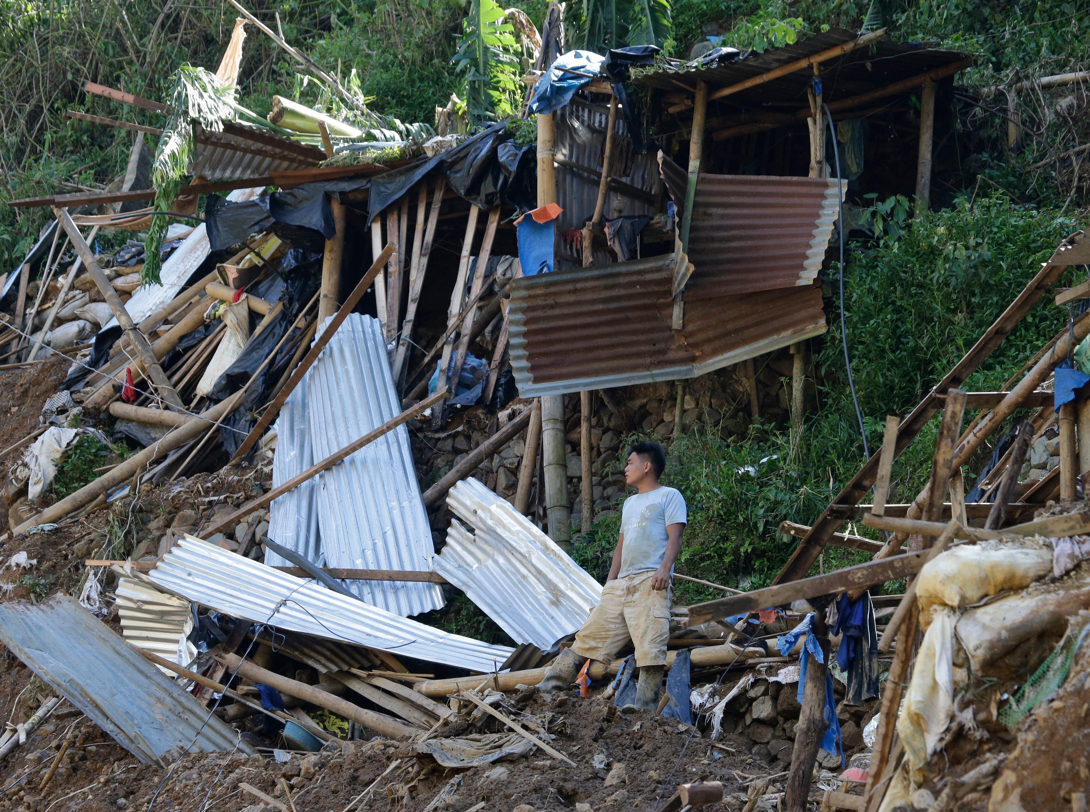 A resident stands beside toppled houses at the site where victims are believed to have been buried by a landslide after Typhoon Mangkhut lashed Itogon, Benguet province, northern Philippines on Monday, Sept. 17, 2018. Itogon Mayor Victorio Palangdan said that at the height of the typhoon's onslaught Saturday afternoon, dozens of people, mostly miners and their families, rushed into an old three-story building in the village of Ucab. The building, a former mining bunkhouse that had been transformed into a chapel, was obliterated when part of a mountain slope collapsed.